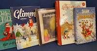 En rad böcker om julen för barn står i en soffa
