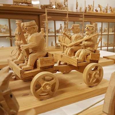 Snidade träfigurer av soldater med gevär som sitter på en vagn