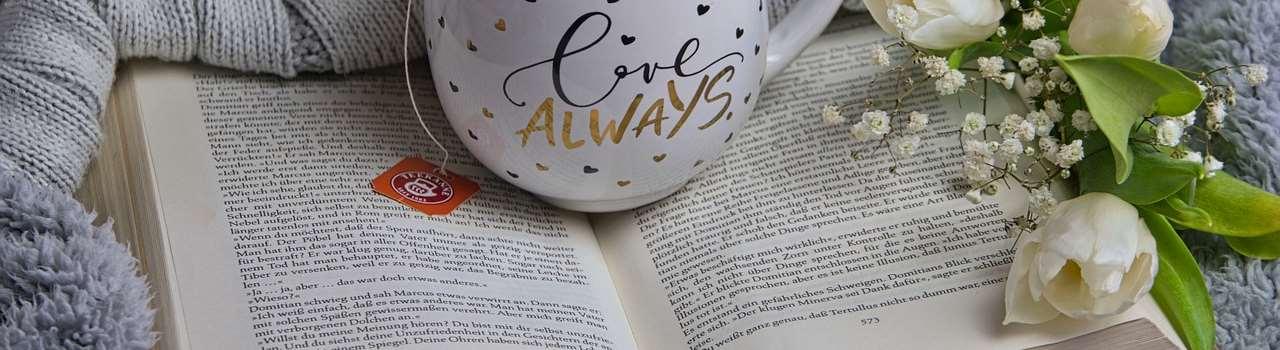 En uppslagen bok ligger på en filt med en tekopp ställd på boken och en tröja och blommor ligger runt om runt