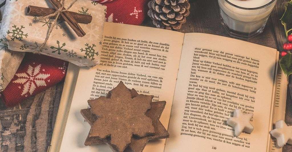 En uppslagen bok bland pepparkakor, julgodis, jultröja och julpynt.