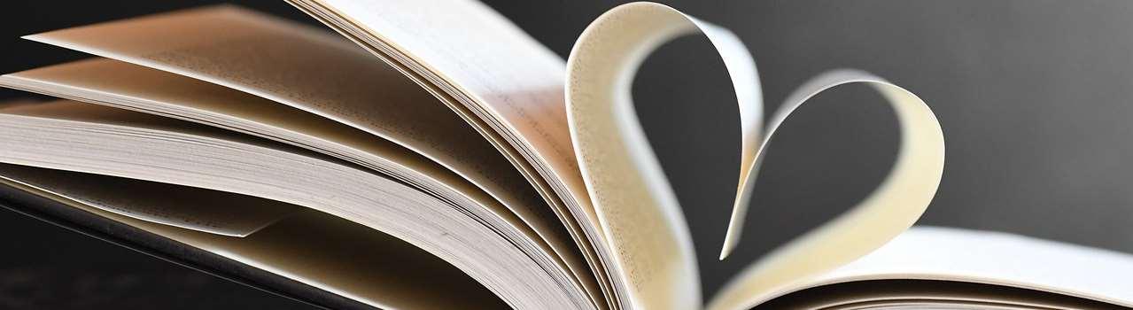 En öppen bok där ett par sidor formats till ett hjärta