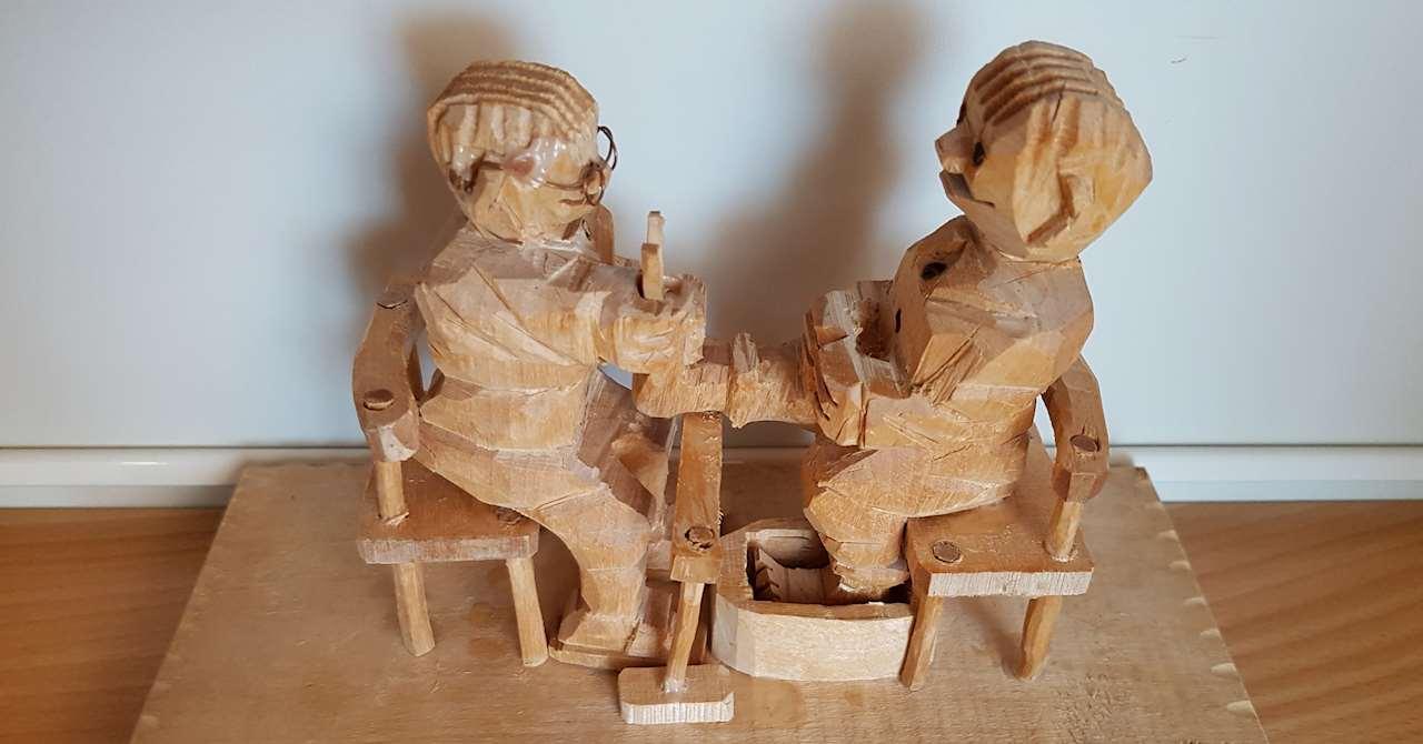 Snidad träfigur där Arthur sitter på en stol framför en fotterapeut