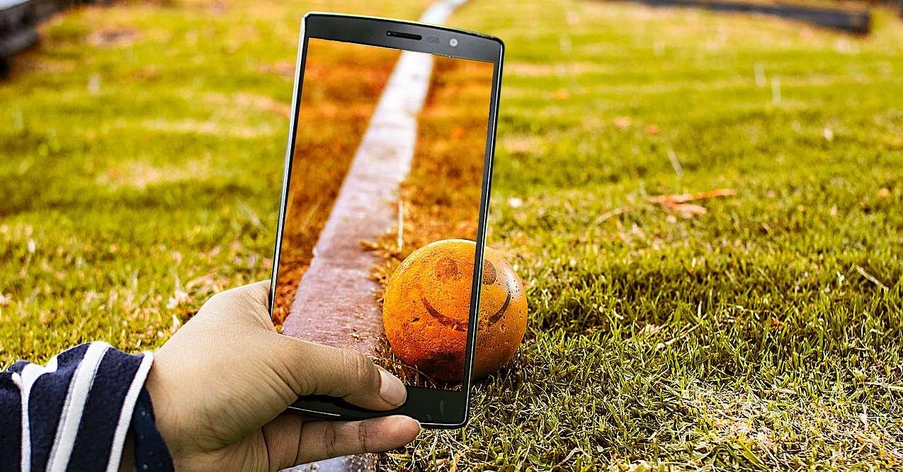 En person fotar ett järnvägsspår och en boll med en smiley på med gräs runt med en mobiltelefon