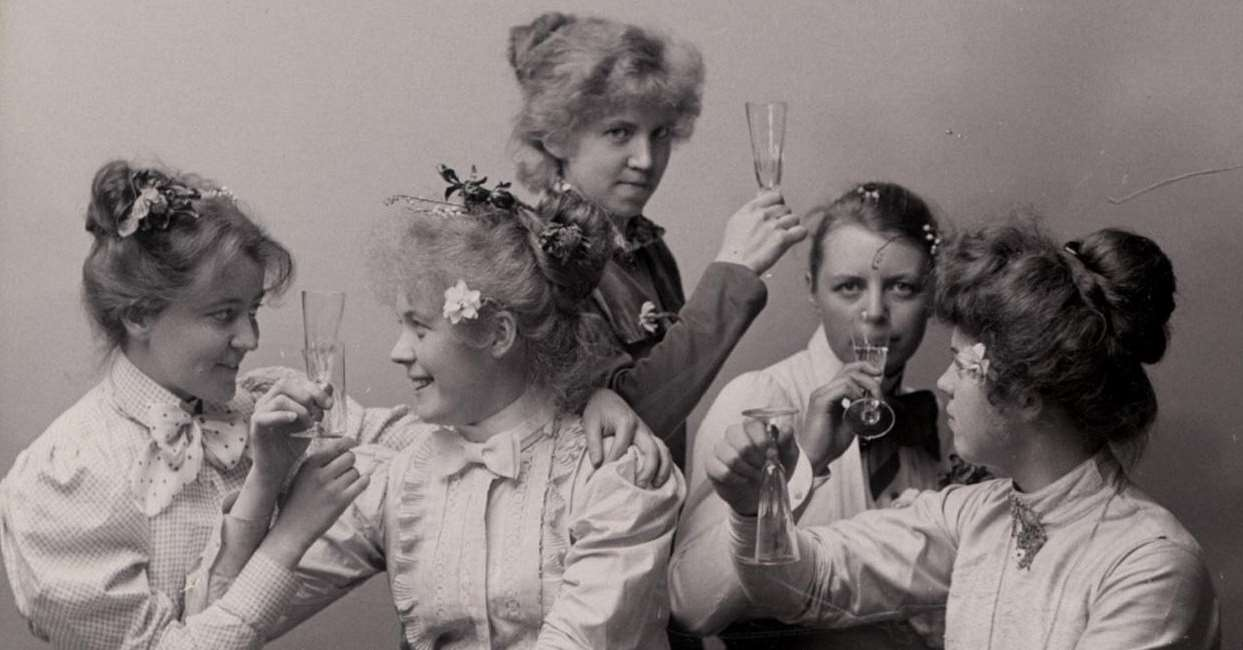Svart-vitt foto av fem kvinnor som skålar för att fira kvinnlig rösträtt 1921